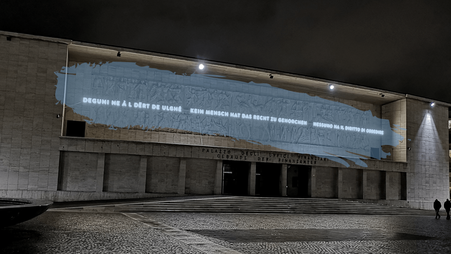 Facade of the former headquarter of the Fascist party in Bozen-Bolzano now displaying a quote by Hannah Arendt. The image has been edited with a translucent splash of blue paint across the relief.